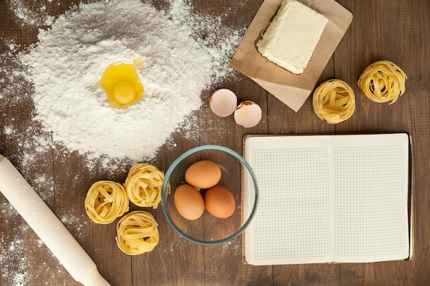 Cooking some tasty food and writing down recipe in open clear note. with ingredients like butter, eggs, flour, pasta.