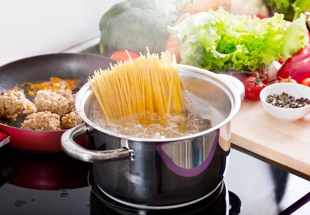 Готовим спагетти в кастрюле с кипятком на плите на кухне