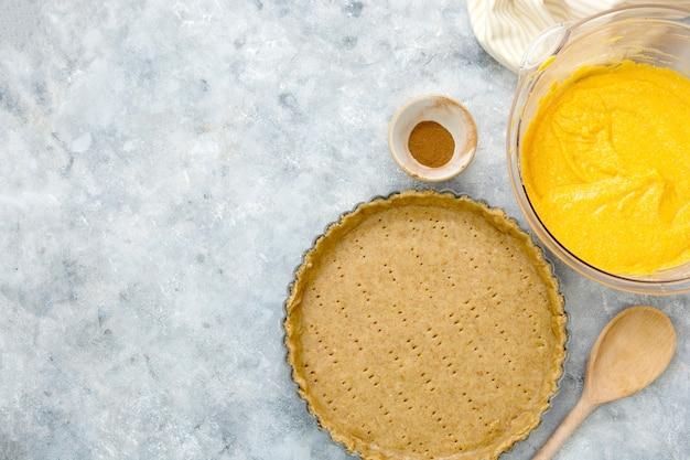 Cooking squash pie or pumpkin tart. top view of crust and pumpkin filling. autumn dessert.