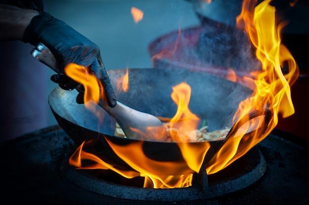 熱いフライパンで屋台の食べ物を調理する
