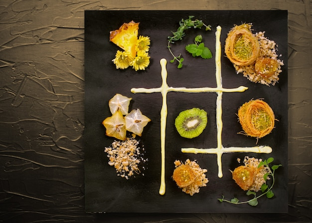 Cooking sweets turkish traditional ramadan pastry dessert kunafa (kadaif, baklava),kiwi,ananas,nuts ,dark  background.plate art composition.