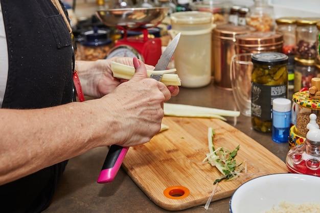 インターネットのレシピでスイスフダンソウを調理し、シェフがフダンソウの茎を切ります。