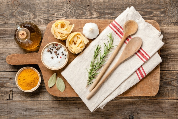 Cooking table with vintage cutting board, spoons and ingredients