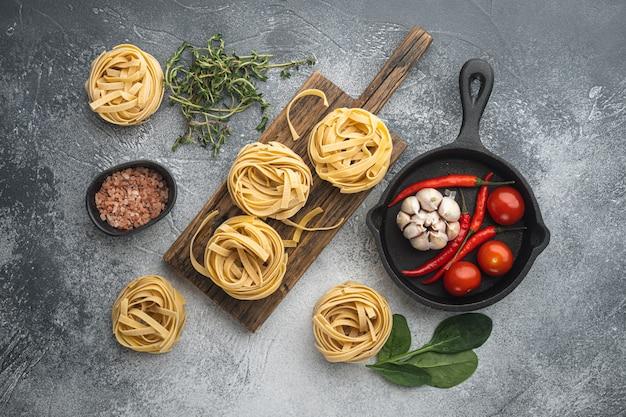 Приготовление пасты тальятелле и набор ингредиентов на сером каменном столе, плоская планировка, вид сверху