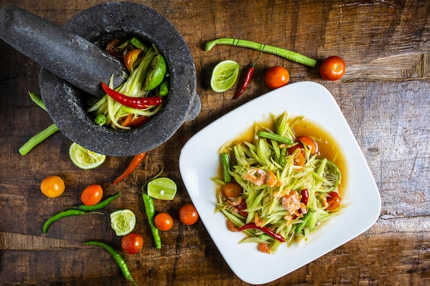 Cooking thai food, papaya salad and papaya salad in a dish with a serving on a wooden table.