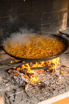 불씨와 야채로 발렌시아 빠에야 쌀 요리하기