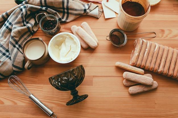 Концепция приготовления тирамису, ингредиенты для приготовления итальянского десерта на деревянном столе, процесс приготовления традиционного торта сверху
