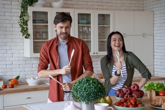 で健康的な料理を準備しながら楽しんで幸せで美しい若い家族のカップルを一緒に料理