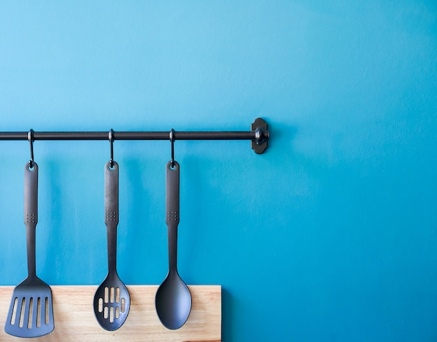 Cooking utensil hanging on the kitchen wall, blue minimal spoon household background with