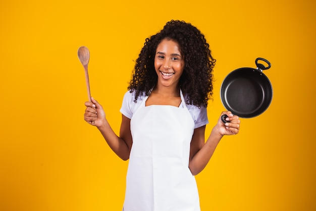 조리기구. 프라이팬과 나무 숟가락으로 부엌에서 요리하는 여자. 춤추는 주부.