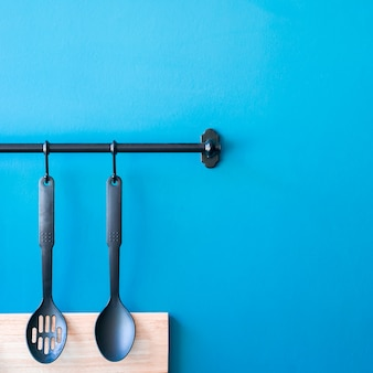 Cooking utensils hanging on the kitchen wall,blue minimal spoon household background with
