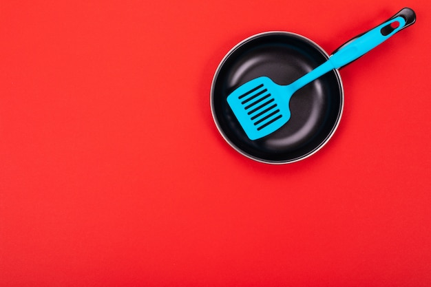 Cooking utensils in kitchen isolated with copyspace on red