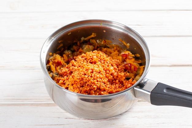 木製のテーブルの上の鍋でナスとレンズ豆と野菜スープを調理します。健康的な野菜のレシピ