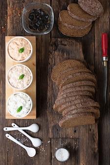 木製のテーブルでベジタリアンスペインのタパスピンチョスサンドイッチを調理する