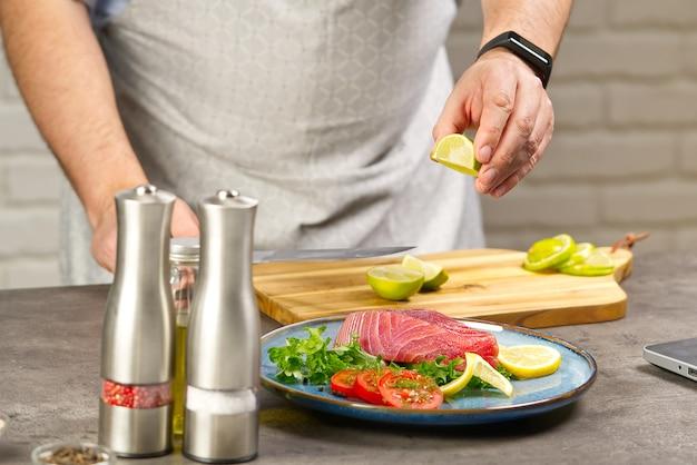 가정 부엌에서 노트북 참치 스테이크 요리 온라인 요리 레시피 개념 생선 집에서 요리