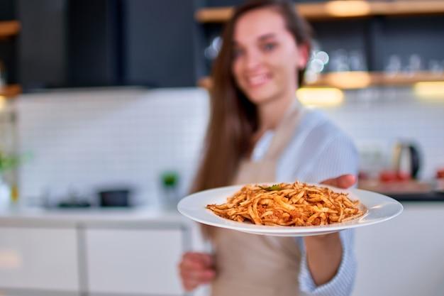 パスタプレートを持っている料理の女性シェフ