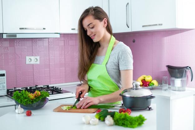 健康的な新鮮なサラダや自宅の台所で料理の完熟野菜を刻んで調理女性。夕食の調理準備