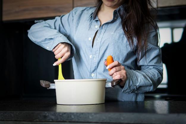 スプーンでキッチンで女性を調理します。若い妻がキッチンのインテリアでボルシチを調理します。