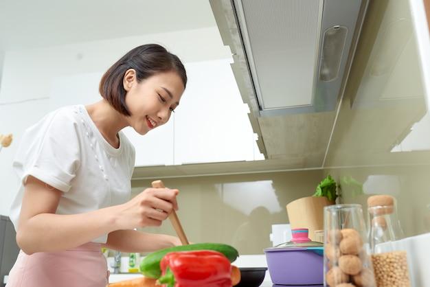 木のスプーンでキッチンで女性を料理
