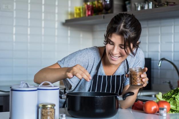 台所で料理をする女性 Premium写真