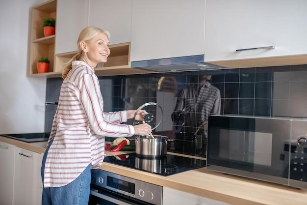 Приготовление еды. женщина, стоящая у плиты на кухне