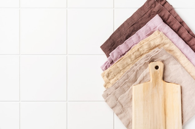 Cooking wooden cutting board and cotton kitchen napkin or towel over on white kitchen wall table. food cooking template concept. copy space wall. top view.