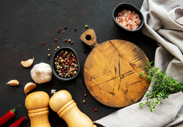 Cooking wooden utensils, empty cutting board and spices