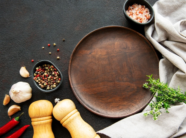 Cooking wooden utensils, empty plate and spices