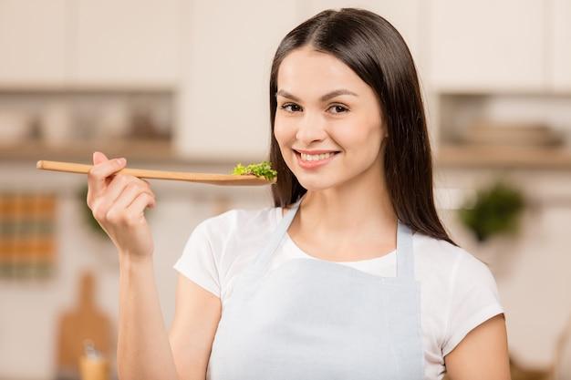 Приготовление молодой женщины на кухне деревянной ложкой. концепция пищевого блоггера. улыбается, смотрит в камеру. крупный план.