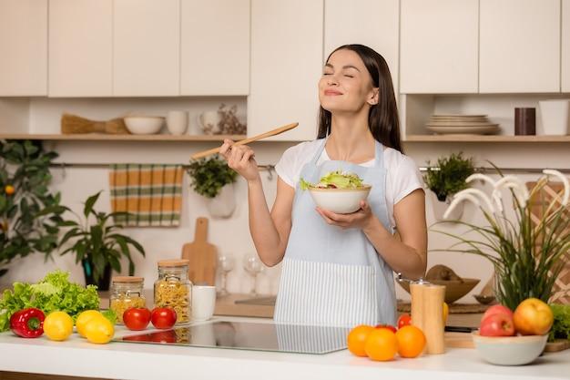 Приготовление молодой женщины на кухне деревянной ложкой. пробует еду. концепция пищевого блоггера. улыбается.