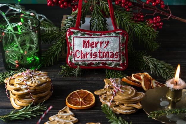 クリスマスツリーの枝、装飾、ジンジャーブレッドcookis、暗い木のメリークリスマス看板