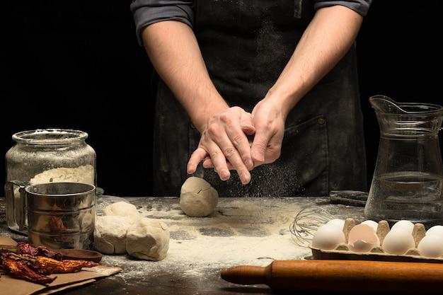 料理人の手は白い小麦粉と木製のテーブルの上で生地を転がしています