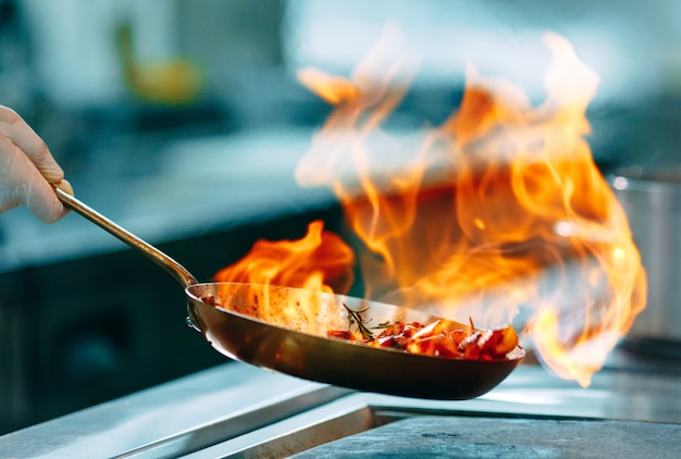 Cooks prepare meals on the stove in the kitchen of the restaurant or hotel.