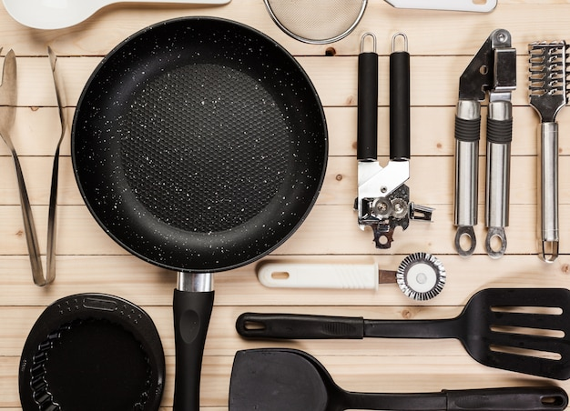 Cookware and accessories on a wooden table.