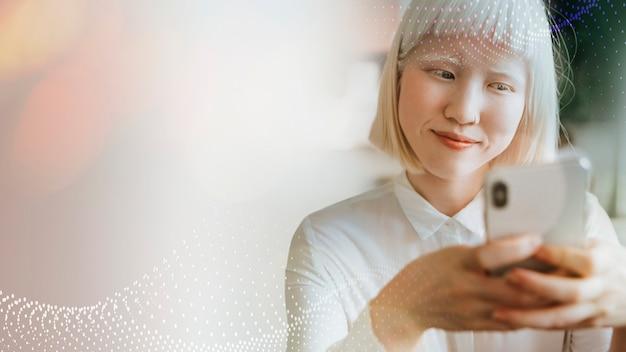 Bella donna albina che manda un sms sul suo telefono in un caffè