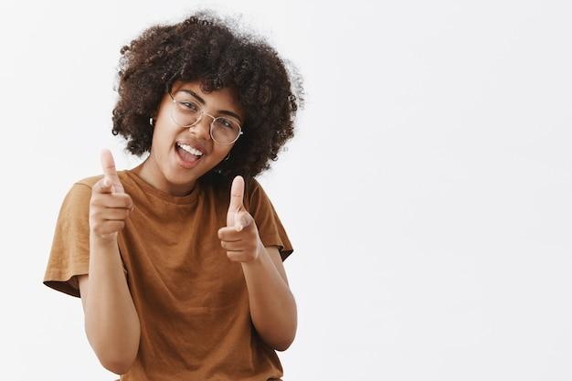 クールでのんきな遊び心のある浅黒い肌の女性と透明なメガネ、茶色のtシャツの顔を傾けて頭を傾け、指銃ジェスチャーで指さす