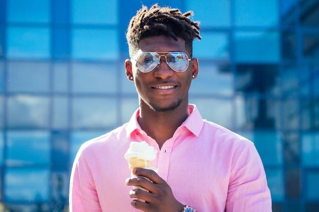 Крутой и модный афроамериканец дреды в солнечных очках ест мороженое в вафельном рожке летом в парке.
