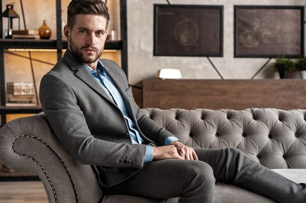 クールでハンサム。屋内で時間を過ごしながらソファに座っているフルスーツの格好良い若い男。
