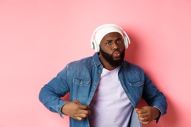 멋지고 건방진 흑인 남자가 춤을 추고, 헤드폰으로 음악을 듣고, 자신감이 있어 보이고, 분홍색 배경 위에 서 있습니다. 복사 공간