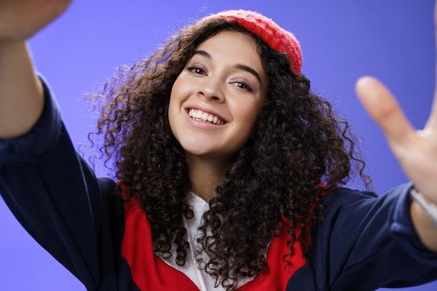 クールでスタイリッシュなフレンドリーな外観の元気いっぱいの20代の幸せな女性。巻き毛が暖かいビーニーを身に着け、屋外の服を着て、青い壁に笑みを浮かべて、自分撮りをしながらカメラを持って頭を傾けています。