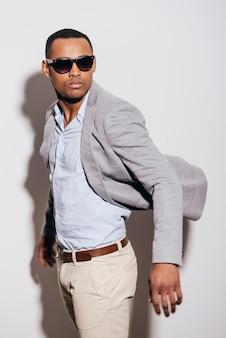 시원하고 트렌디합니다. 재킷을 입고 어깨 너머로 보이는 선글라스를 쓴 자신감 있는 젊은 아프리카 남자