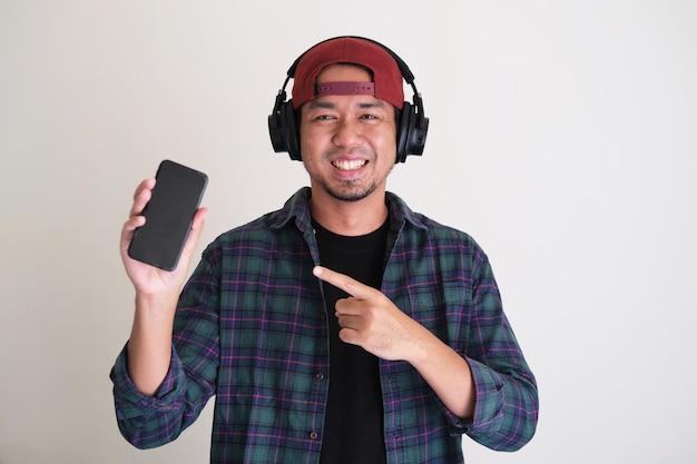 멋진 아시아 남자가 웃고 손가락으로 휴대전화를 가리키고 있습니다.