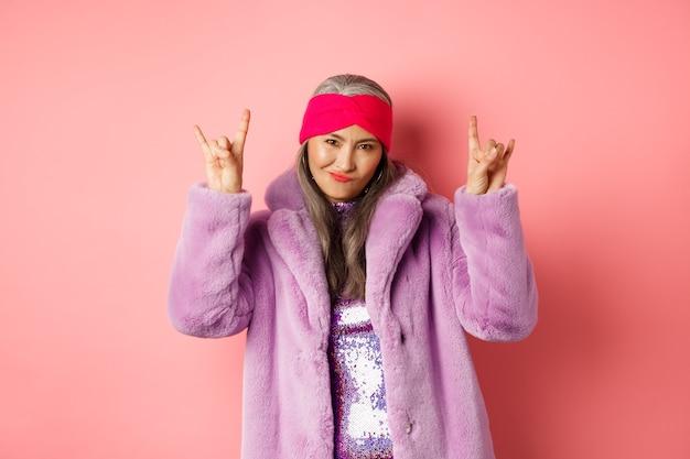 ファッショナブルなフェイクファーのコートを着たクールなアジアの成熟した女性、ロックンロールの角の兆候を示し、カメラで生意気な笑顔、楽しんで、ピンクの背景の上に立っています。