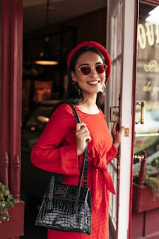 Cool attractive brunette woman in stylish red dress, trendy bright beret and sunglasses opens leathered black handbag and opens cafe door
