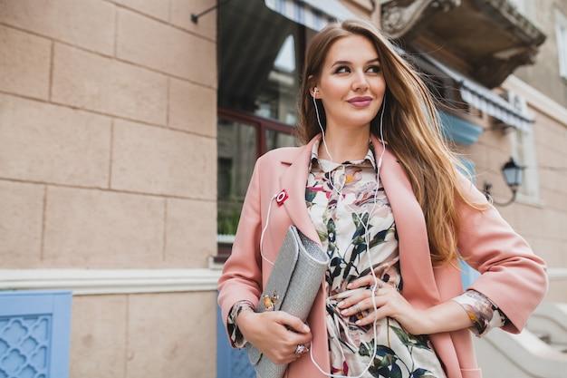 クールな魅力的なスタイリッシュな笑顔の女性が街を歩いてピンクのコート春のファッショントレンドの財布を持って、イヤホンで音楽を聴く