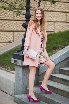 クールな魅力的なスタイリッシュな笑顔の女性がピンクのコートで街を歩く