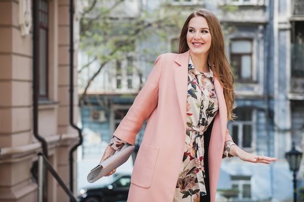 Raffreddare attraente elegante donna sorridente a piedi la strada della città in rosa cappotto primavera tendenza moda che tiene la borsa