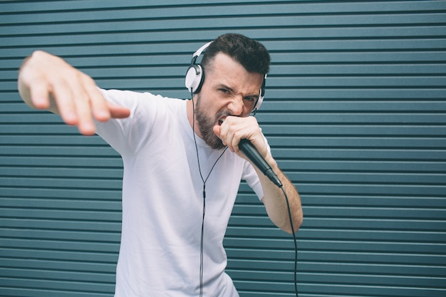 Cool and awesome man is reading rap in microphone. he is showing his hand and looking at camera. guy is singing in mic and wears headphones. isolated on striped