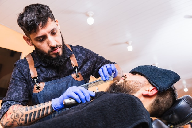 Крутой татуированный парикмахер работает в парикмахерской. парикмахер работает над бородой хипстера. парикмахер с помощью электрического ножа и расчески.