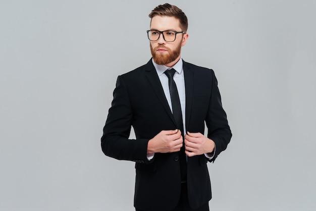 안경과 검은 양복을 입은 멋진 수염 사업가가 옆으로 쳐다보고 있습니다. 격리 된 회색 배경